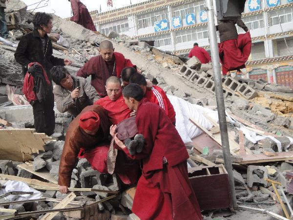 Local people succor the injured persons from the debris of crumbled houses shortly after an earthquake jolted at 7:49 a.m., at Gyegu Town, of Yushu, a Tibetan autonomous prefecture in western Qinghai Province of northwest China, April 14, 2010.(Xinhua/Zhang Hongshuan)
