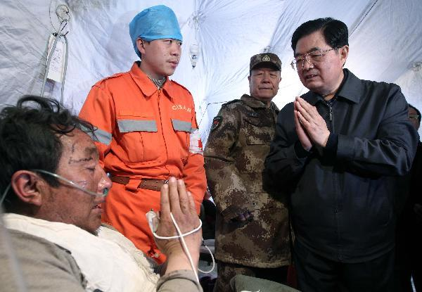 Chinese President Hu Jintao (1st R) talks to an injured man during his visit to those injured in the quake receiving treatment at a stadium in the Tibetan Autonomous Prefecture of Yushu, northwest China Qinghai Province, April 18, 2010. Hu arrived in Yushu Sunday morning to direct relief work. (Xinhua/Lan Hongguang)