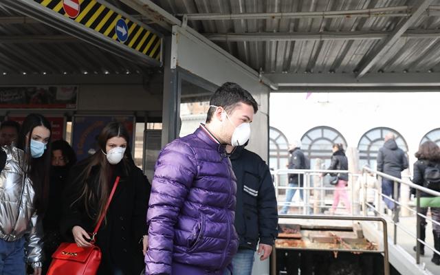 2月23日,在意大利威尼斯,戴着口罩的游客准备乘坐公交船。