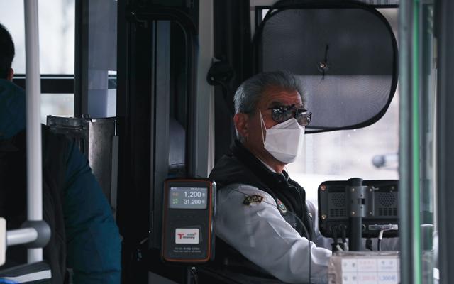 21日在首尔市的钟路区,一名戴口罩的公交车司机靠站停车。