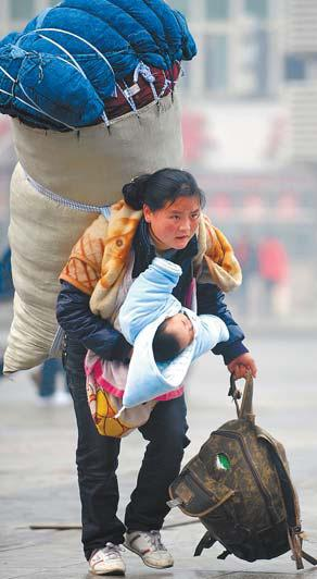 A woman staggers under the load of carrying a child and heavy baggage as she tries to reach Nanchang railway station in Jiangxi province over the weekend. About 2.5 billion trips are expected over 40 days starting from Saturday.[China Daily/Zhou Ke]