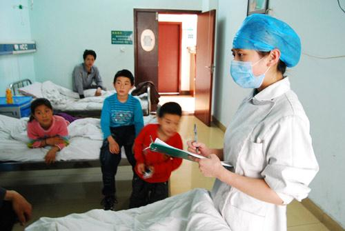 A nurse inquires of lead-poisoned children on their sickening matters, at the Chenzhou Municipal Hospital of Traditional Chinese Medicine, as most of the patients were in stable condition in Chenzhou, central China's Hunan Province, March 21, 2010. The Chenzhou Municipal Hospital of Traditional Chinese Medicine received 10 more children Sunday, bringing the number of patients tested to have excessive levels of lead in their blood to 29, 28 of whom were below the age of 14. The cases emerged about 10 months after 254 children were found with excessive levels of lead in their blood in Chenzhou in July last year. A local factory held accountable for discharging contamination, which caused the poisoning, was closed. (Xinhua Photo)