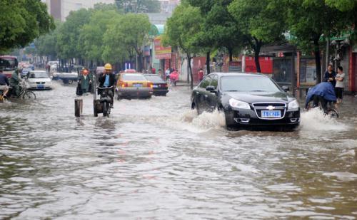 VehiclesrunonafloodedstreetinNanchang,capitalofeastChina'sJiangxiProvince,onMay8,2010.HeavyrainhitNanchangonSaturdayandcausedfloodinthecity.(Xinhua/ZhouKe)