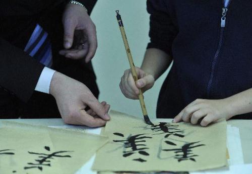 AChinesediplomatteachesaBelgianchildtouseChinesebrushpenattheOpenDayoftheChineseMissiontotheEuropeanUnioninBrussels,capitalofBelgium,May19,2010.Some500localresidentsattendedtheOpenDayactivitytolearnmoreaboutChina.(Xinhua/WuWei)