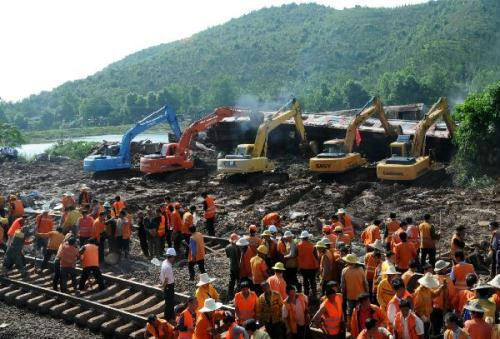 Workers remove the mud and rocks at the landslide site in Dongxiang County, east China's Jiangxi Province, May 23, 2010. All the nine derailed cars were removed from the site after the accident on Sunday. The train derailed after hitting a section of track that had been damaged in a landslide, and then the Shanghai-Kunming railway line was closed. (Xinhua/Chen Chunyuan)