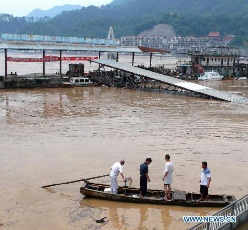 People take a boat at a flooded transport dock in Nanping City, southeast China's Fujian Province, June 20, 2010. Caused by continual torrential rains since June 18, rivers continued to swell in Nanping City, leaving 24 dead and 28 lost so far.(Xinhua/Wang Shanglin)