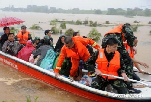 Paramilitary policemen help evacuate residents from Wanjia village of Fuzhou City, East China's Jiangxi province, June 22, 2010. Days of heavy rain burst the Changkai Dike of Fu River on June 21, threatening the lives of 145,000 local people. Local authorities have ordered immediate evacuation, and the army and paramilitary police have begun conducting rescue operations.(Xinhua Photo)