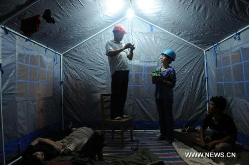 Electricians fix live wires in a makeshift tent serving for the people affected by floods in Wuzhou City of east China's Jiangxi Province, June 23, 2010. A total of 17 evacuation centers in Wuzhou had received 20,014 people affected by floods until 19:00 Wednesday.(Xinhua/Zhou Ke)