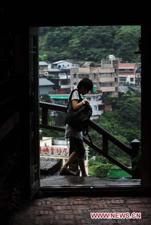 A tourist walks on an old street in the town of Jioufen in Rueifang Township of Taipei County, southeast China's Taiwan, June 23, 2010.