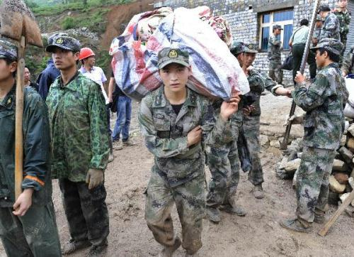 Rescuerscarrybundlesofparcelsforlocalvillagersatthelandslideruins,inDazhaiVillage,GangwuTownship,ofGuanlingBouyei&MiaoAutonomousCounty,southwestChina'sGuizhouProvince,June29,2010.(Xinhua/PengNian)