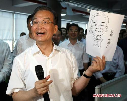 Chinese Premier Wen Jiabao smiles while showing a cartoon presented by a worker in Talkweb Information System Co., Ltd. in Changsha, capital of central China's Hunan Province, on July 2, 2010. Wen Jiabao made an inspection tour to Changsha recently.(Xinhua/Yao Dawei)
