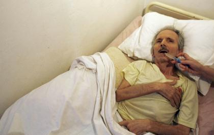 Alzheimer's disease patient Carlos Alberto Henriques, 65, drinks water through a syringe with the help of his wife Maria Elvira Boavida (unseen) in their house in Lisbon September 15, 2009. (Xinhua/Reuters File Photo)