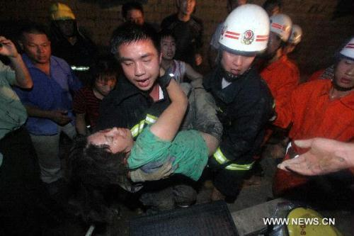 Rescuers carries out a survivor from the site of a building collapse accident in Cangshan District of Fuzhou, capital of southeast China's Fujian Province, July 6, 2010. At least one person died after a 3-story brick-concrete residential building collapsed here Tuesday and buried a dozen in the wreckage, rescuers said. By Tuesday midnight, rescuers have pulled out 10 survivors and one body from the debris. The search is continuing for the last one who is still missing. (Xinhua/Zhu Xiaohang)