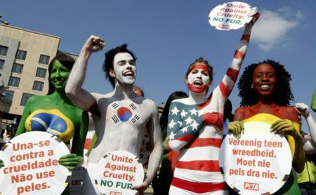Protestors painted in the colours of flags of various countries hold signs and chant slogans during a demonstration against the fur industry in Johannesburg July 8, 2010. According to the PETA website, the event led by FHM model Candice Brink and participated by protestors from People for the Ethical Treatment of Animals (PETA) Asia, Fur Free South Africa and the South African Naturist Federation will highlight the plight of animals used in coats and other clothing items.(Xinhua/Reuters Photo)