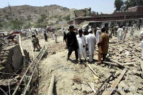 Local residents gather at the site of blast in northwest Pakistan's Mohmand Agency July 9, 2010. (Xinhua/Umar Qayyum)