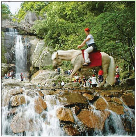 A visitor riding on a horse in front of a waterfall on Mount Tiantai.