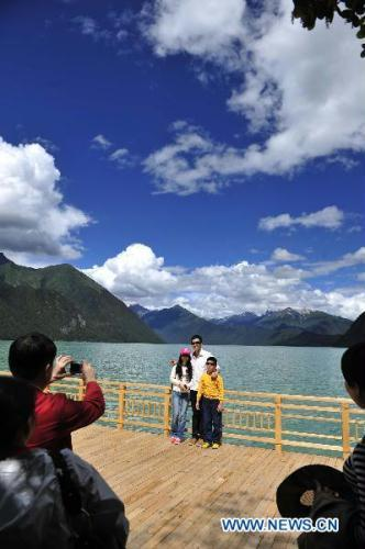 Tourists take photos at a scenic spot in southwest China's Tibet Autonomous Region, July 13, 2010. (Xinhua/Hao Tongqian)