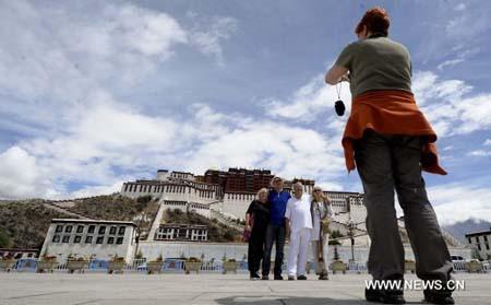 TouriststakephotosatthesquareinfrontofthePotalaPalaceinLhasa,capitalofsouthwestChina'sTibetAutonomousRegion,June22,2010.Tibethosted1,800,000touristsinthefirstsixmonthsof2010,up20.3%year-on-year.Thetourismrevenuejumped23.6%year-on-yearto1.39billionyuan(205millionU.S.dollars).(Xinhua/PurbuZaxi)