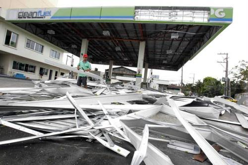 A worker inspects a roof damaged by Typhoon Conson in front of a gas station in Manila July 14, 2010. Typhoon Conson cut power supplies across Metro Manila and surrounding provinces as it swept across the main Philippine island of Luzon to the South China Sea and headed towards southern China on Wednesday.(Xinhua/Reuters Photo)