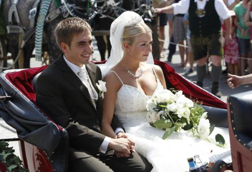 Germany's national soccer captain Philipp Lahm and his new wife Claudia leave the church of Kleinhelfendorf near Munich in a carriage after their marriage ceremony July 14, 2010.(Xinhua/Reuters Photo)
