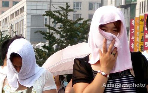 Women cover their heads with towels to cool themselves from heat in Beijing on July 24, 2010. High temperatures in the city in recent days has led many residents to look for ways to cool down.[Photo/Asianewsphoto]