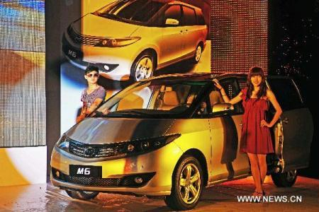 "Models pose with a car made by Chinese automaker BYD during a press conference in Hangzhou, capital of east China's Zhejiang Province, July 27, 2010. The BYD automaker issued its ""M6"" car to the market of east China on Tuesday. (Xinhua/Tan Jin)"