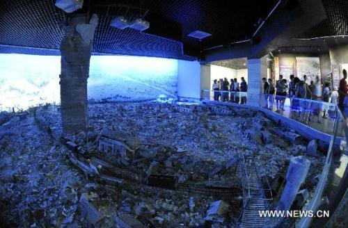 Tourists visit the Tangshan Earthquake Museum in Tangshan, north China's Hebei Province, July 28, 2010. The Tangshan Earthquake Museum is located inside the Tangshan Earthquake Memorial Park. Opened Wednesday, the museum covers an area of some 4,000 square meters with some 400 pieces of exhibits of photographs and 300 material objects. (Xinhua/Yang Shiyao)