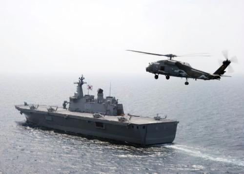 "A SH-60F Sea Hawk helicopter assigned to the Chargers of Helicopter Anti-Submarine Squadron (HS) 14 flies near the Republic of Korea amphibious ship Dokdo (LPH 6111) in the East Sea of Korea, July 27, 2010. The Republic of Korea and the United States are conducting the combined alliance maritime and air readiness exercise ""Invincible Spirit"" in the seas east of the Korean peninsula from July 25-28, 2010. This is the first in a series of joint military exercises that will occur over the coming months in the East and West Seas. (Xinhua/Reuters)"