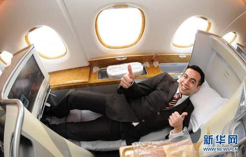 A steward gestures as he shows the interior design in business class of the Emirates Airlines' A380 passenger plane which arrives at the Capital International Airport in Beijing August 1, 2010.(Xinhua/Wang Jianhua)