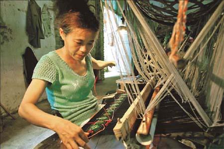 "A weaver operates a ""primitive"" loom nicknamed ""the pig basket"". Photos by Huo Yan / China Daily"