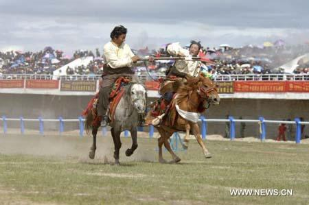 Two riders perform during the opening ceremony of annual horse racing festival in Nagqu County, southwest China's Tibet Autonomous Region, Aug. 10, 2010. The one-week horse racing festival kicked off in Nagqu on Tuesday. (Xinhua photo)
