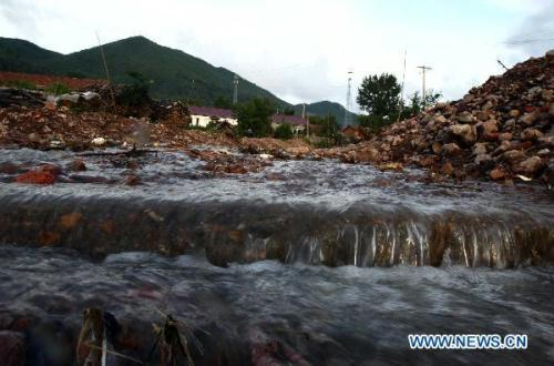 Photo taken on Aug. 10, 2010 shows a flooded road in Weishahe Township of Linjiang, northeast China's Jilin Province. Torrential rain attacked Linjiang on July 31, with a record-high precipitation of 165.3mm. The rain-triggered flood resulted in cut of water and power supply in towns, leaving 9 dead and 3 missing. (Xinhua/Yuan Man)
