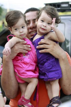 Siamese twins Hannah Yinneth (L) and Hannah Yanneth are carried by their father Alfredo Fernandez as they attend their first birthday party in Panama City August 14, 2010. The sisters, who are joined at the liver, will undergo an operation on August 23 that aims to separate them. Their mother, Sara Gil, 21, said although she hopes the twins' lives will be better when they are separated, there is a possibility that one or even both of them could lose their lives as a result of the operation.(Xinhua/Reuters Photo)