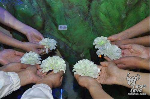 Gansu Provincial pavilion staff members use hand-make silk flowers that they made by themselves to mourn mudslide victims.