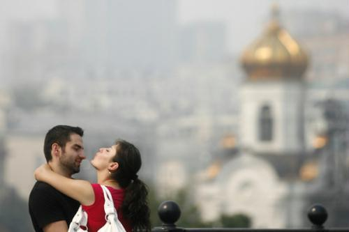A couple embrace, with buildings shrouded in smog in the background, in central Moscow, August 15, 2010.(Xinhua/Reuters Photo)