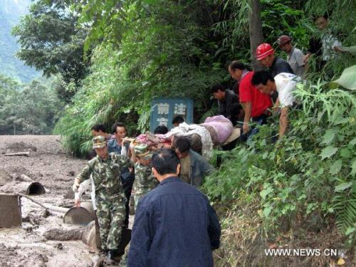 Rescuers carry an injured resident in mudslides-hit Puladi Township of Gongshan Drung-Nu Autonomous County, southwest China's Yunnan Province Aug. 18, 2010. Rain-triggered mudslides occurred here on early Wednesday, causing at least 67 people missing.(Xinhua/Zhong Zhifang)
