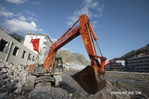 A crane removes barriers to speed up flood discharge in landslide-hit Zhouqu County, Gannan Tibetan Autonomous Prefecture in northwest China's Gansu Province, Aug. 19, 2010. Soldiers hurry up on Thursday to eliminate the barriers in downtown Zhouqu County in order to counteract the effect of rains on Wednesday which slowed down flood discharge. (Xinhua/Ren Zhenglai)
