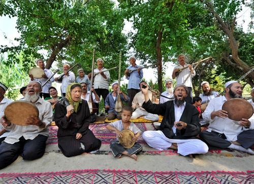 Folk artists in Shche county, Xinjiang Uygur autonomous region, play traditional songs of the 12 Muqams on July 10. Shche is renowned as the hometown of the 12 Muqams, which are ethnic music and songs on the national intangible cultural heritage list.(China Daily)