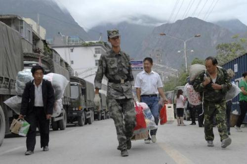 A soldier helps landslide victims move into a newly established shelter site in Zhouqu County, northwest China's Gansu Province, Aug. 25, 2010. Some of the landslide victims moved to newly established and better equipped shelter sites on Wednesday to spare the classrooms for the students in the coming semester. Some of the victims have been settled in the classrooms of schools in Zhouqu County after the landslide. (Xinhua/Hou Jun)