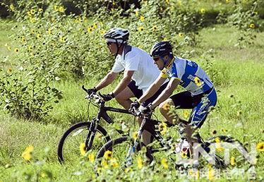 布什与环法冠军阿姆斯特朗在农场里比赛骑车