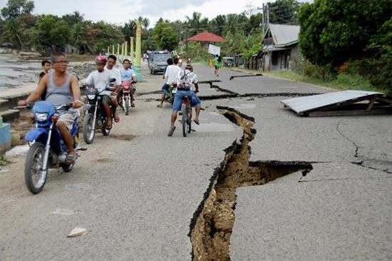 residents drive past cracks in a road caused by an earthquake in negros oriental central philippines feb 6 2012 the magnitude 6 7 earthquake struck the