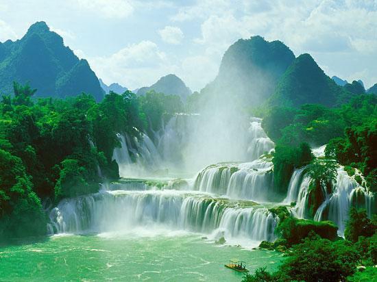 新浪旅游配图:中国境内的德天瀑布 摄影:龙婷   德天瀑布起源于广西靖西县归春河,终年有水,流入越南又流回广西,经过大新县德天村处遇断崖跌落而成瀑布。瀑布宽120米,与越南板约大瀑布并排在崇山之间,总宽度208米,四周古树参天,花草掩映。瀑布景色随季节变化而不同。冬季,瀑水纤秀,多束水流悠然飞落;春季,木棉似火,点缀其间,绿色梯田,相映生光辉;夏季,河水溢涨,激流排山倒海奔腾而下,响声如雷,水雾遮天;秋季,素绢高挂,碧水清流,梯田铺金,水雾夹着阵阵稻香扑面而来,令人陶醉。瀑布流水从80米高的山崖直泻而下,