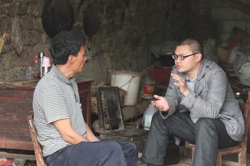 刘习聪在做村民思想工作,让村民把孩子送到学校读书。