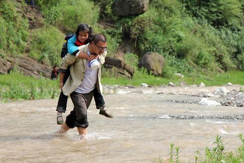 放学后,刘习聪送学生回家,背学生过河。