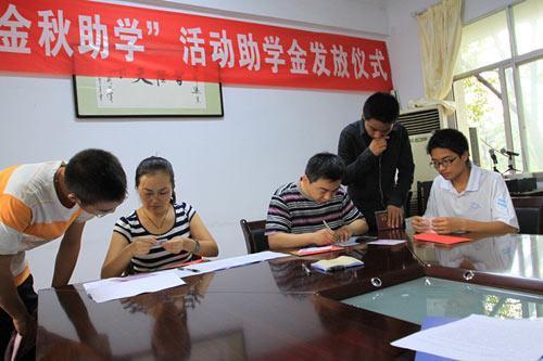 市总工会工作人员认真核实学生身份并发放助学金