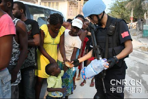 China's anti-riot squad hands out bread to children in Haiti