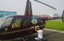 走进广汉,工作人员在停机坪上为直升机贴我们《从农田到餐桌》系列片的标志