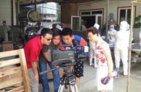 走进广汉,摄制组成员在摄像机的外监视上观看刚刚拍完的素材,旁边的阿姨也一起看了起来