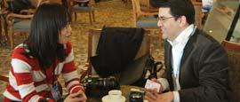 """2010年3月11日,北京,土尔其多安通讯社记者(右)萨蒂・卡伊马兹向中国同行""""打听""""两会新闻。"""