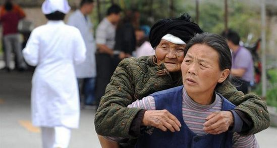 一名头发半百的妇女背着一名老奶奶前来接受治疗。